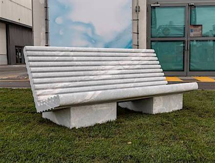 "FLUCTUS: The project involves the design of two types of seat made of natural stone, created with the diamond wire cutting technique. Both seats are called Fluctus; one has a tilted high back (Relax version) but the other (Temporary version) has no flat back. The seat comprises many tiny comfortable ""waves"", which serve to drain off rainwater and provide perfect heat dispersion thanks to the least possible contact between the back and the stone."