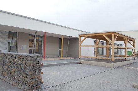 Foto des Eingangsbereichs der Kita, rechts der überdachte Abstellplatz für Kinderwagen. Quelle: Ausschreibung