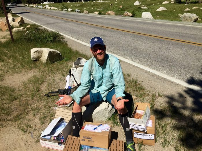 Mountain Man sitting on a pile of care packages