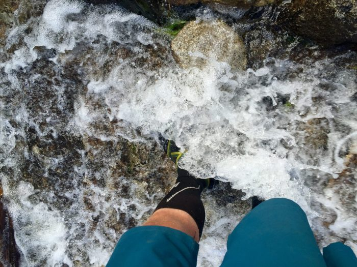 Mountain Man walking through trail full of rushing water