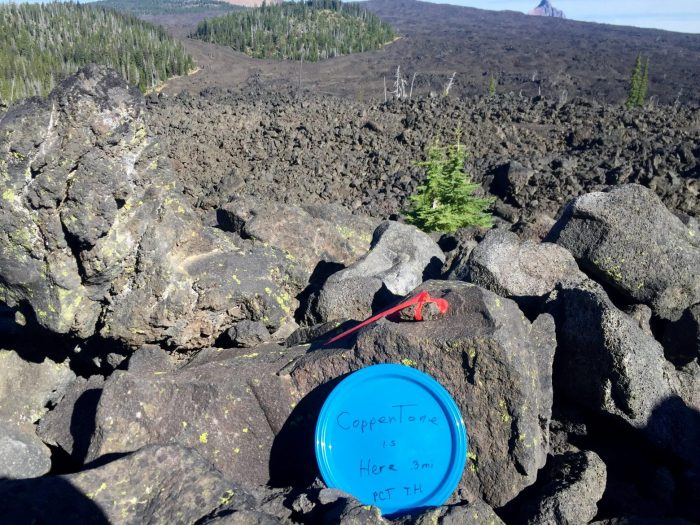 Blue plastic plate among the lava rocks pointing to Coppertone trail magic