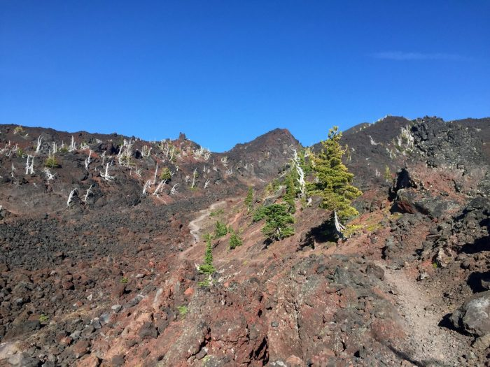 PCT crossing through fields of red and brown lava rocks under a blue sky