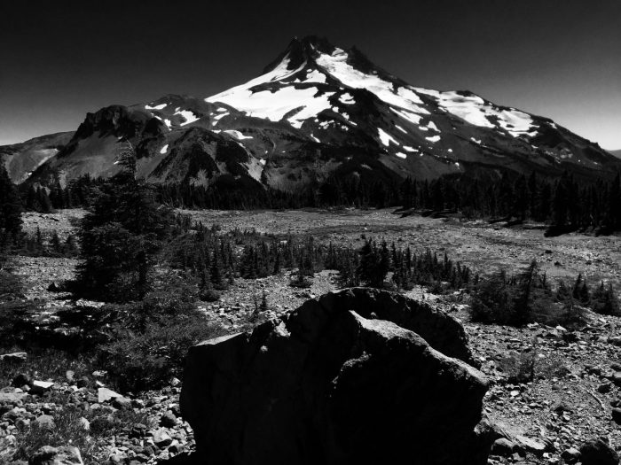 Looking back over a trailside boulder at a snow capped Mount Jefferson