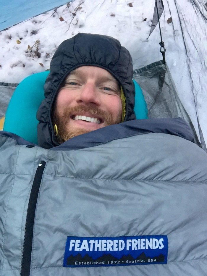 Mountain Man bundled up in sleeping bag on a cold snowy night