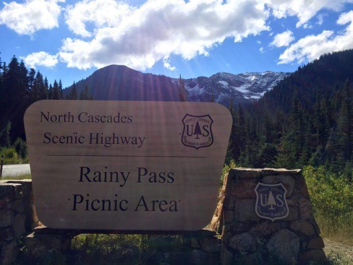 Rainy Pass sign under blue skies