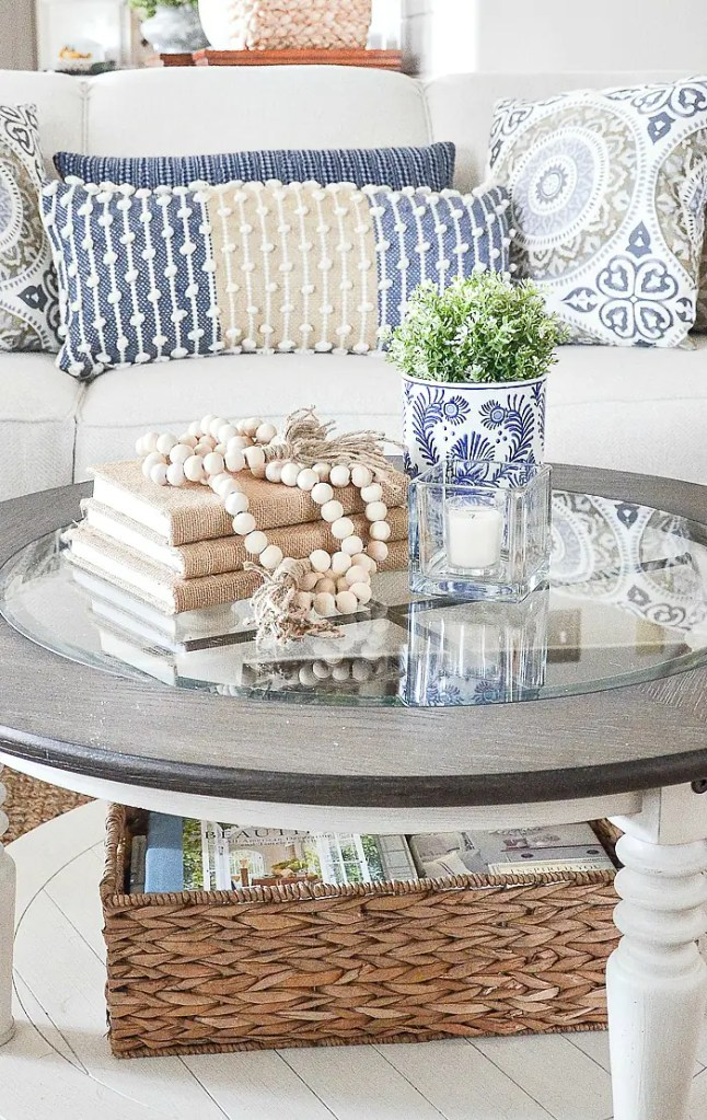 ROUND COFFEE TABLE WTH BURLAP BOOKS AND OTHER ACCENT DECOR ON IT