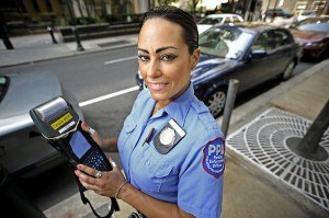 A meter maid writes a violator a ticket
