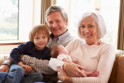 Grandparents With Grandson And Newborn Baby Granddaughter