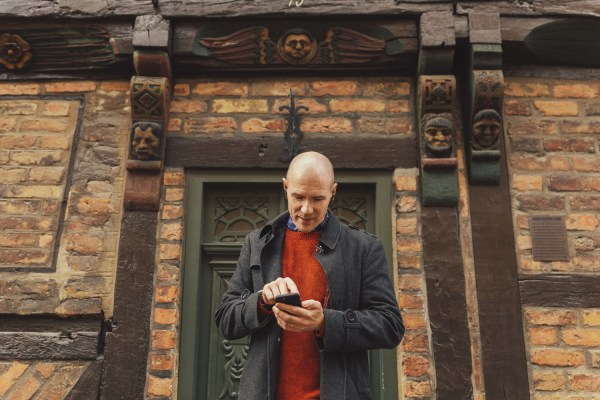 A man is standing in front of a half-timbred house. He is looking at his phone