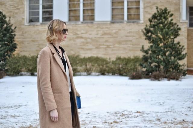 Black and white blouse, blue purse, flare jeans, Karen Walker Super Duper, Ditto, thredUP, tan coat
