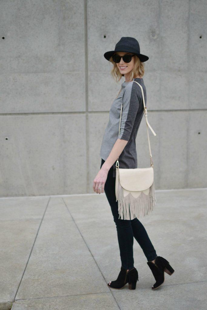grey top, black jeans, fringe bag, fringe booties, hat