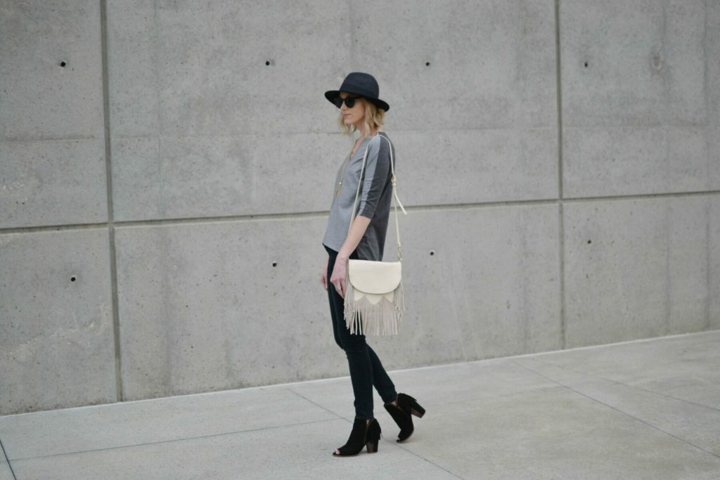 grey top, black jeans, fringe bag walking