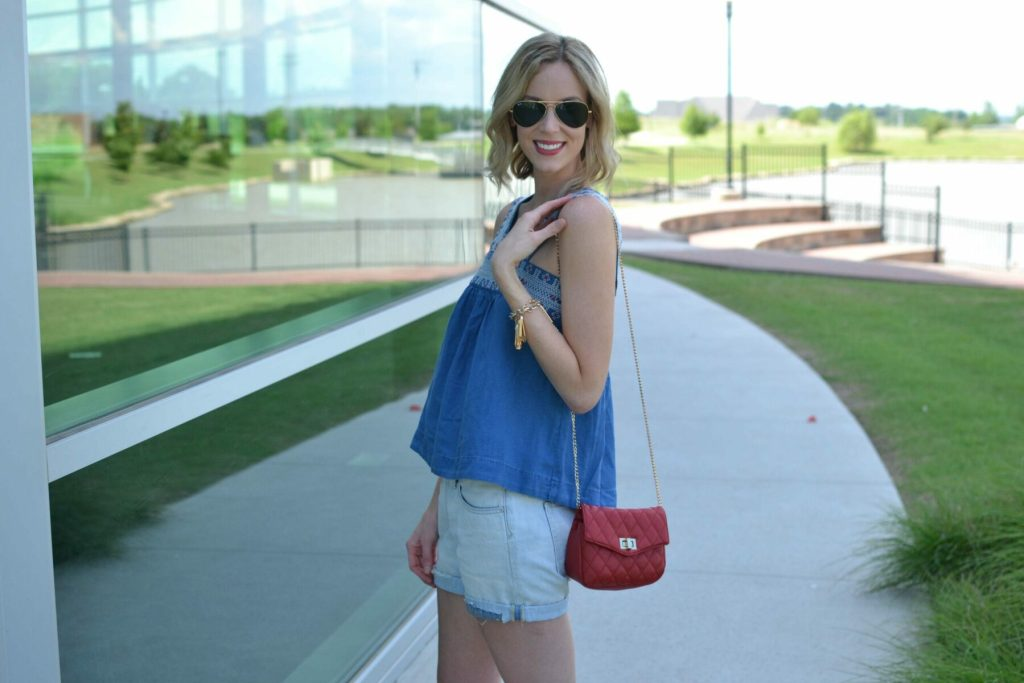 madewell denim top, jean shorts, red bag, fringe bracelet