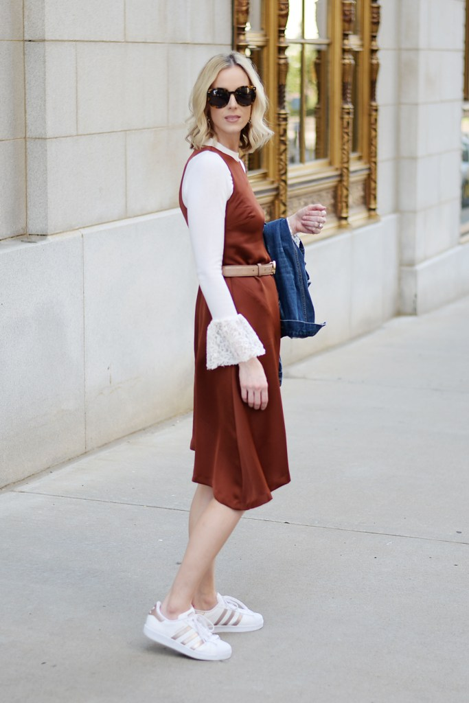 asymmetrical rust colored dress layered over a cream bell sleeve top with adidas superstars and jean jacket