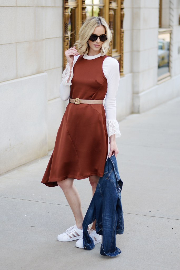 rust colored asymmetrical dress layered over a bell sleeve top with adidas superstars and gucci belt