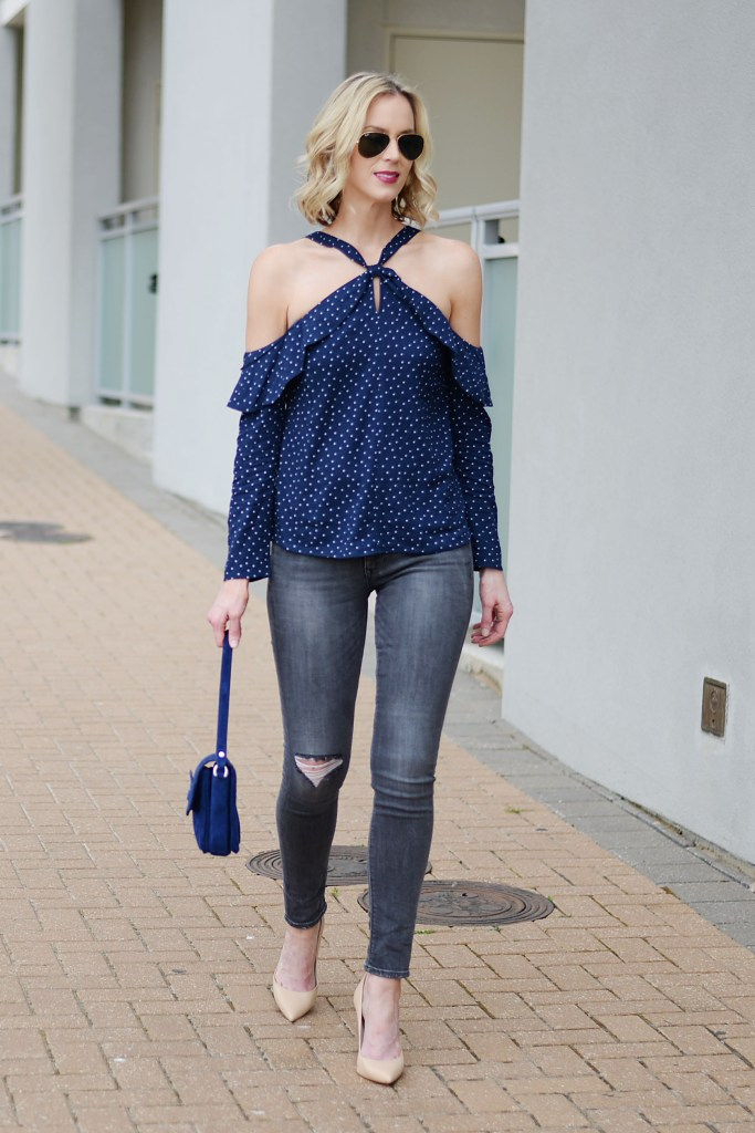 navy polka dot top with halter neck and cut out shoulders, grey jeans, nude heels