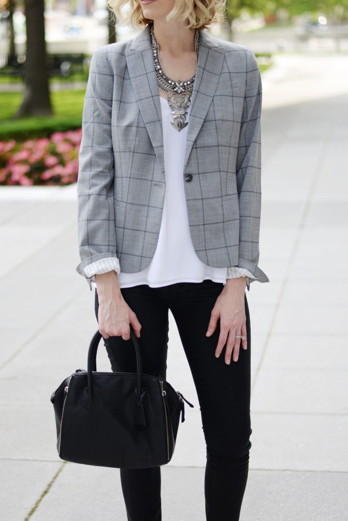 statement silver bib necklace with a blazer and white camisole, black handheld bag