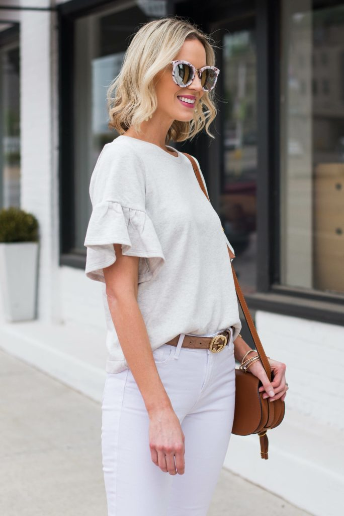 grey flutter sleeve top with white jeans