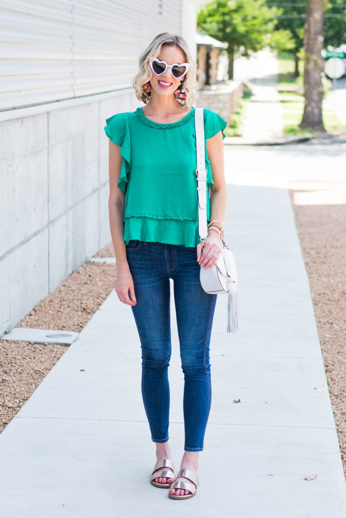 dressy green top with ruffle hem, skinny jeans, white heart earrings