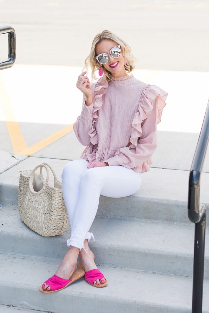 mirrored sunglasses with pink top, white jeans, and bright pink slide shoes