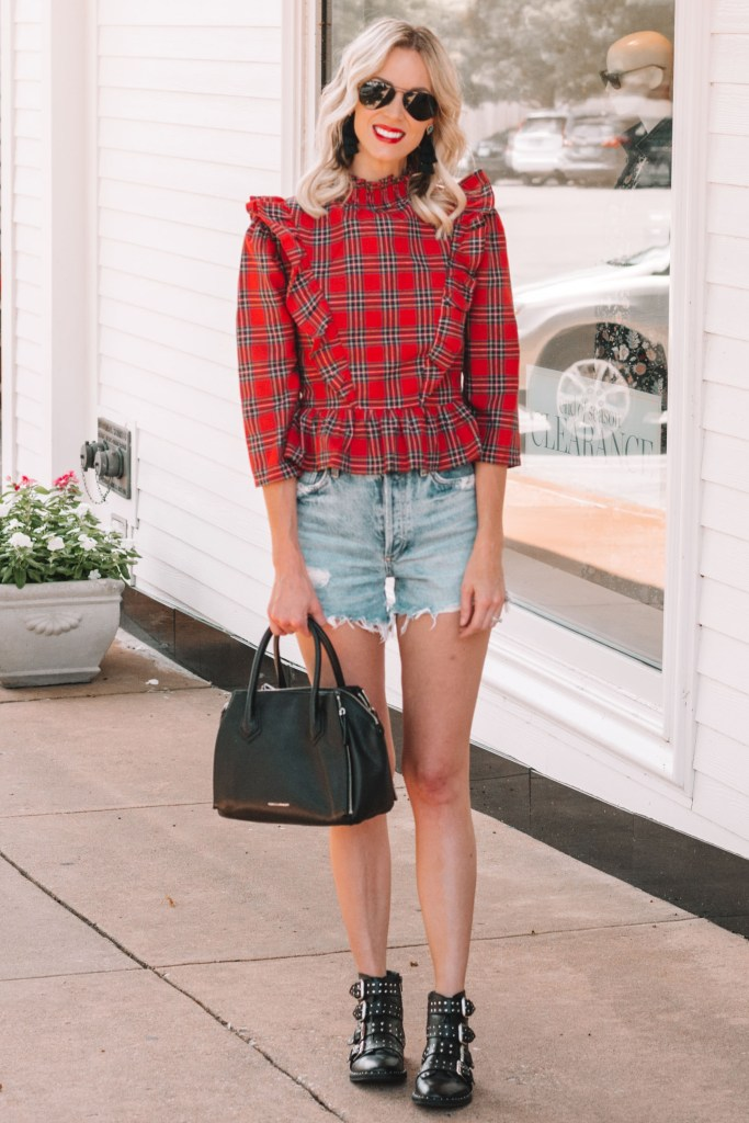 red plaid top with cutoff jean shorts and black buckle boots