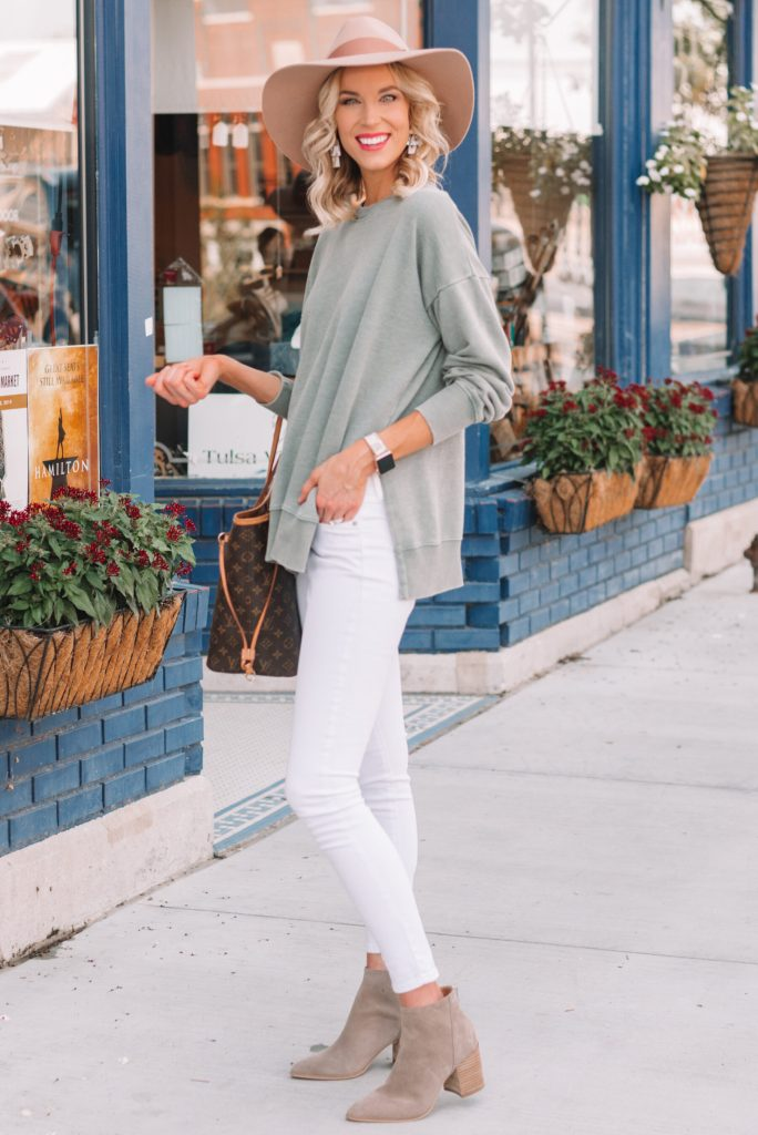mossy green pullover with white jeans and boots