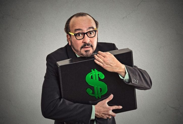 33116588 - money greed. business man holding holding case with dollars tightly isolated on grey wall background. worship, miser, excessive gain, finance concept