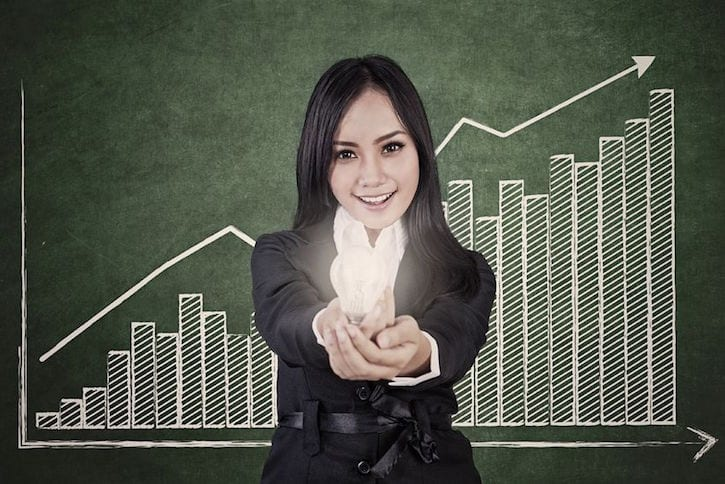17824212 - businesswoman is holding a bright light bulb with profit bar chart showing increase in value