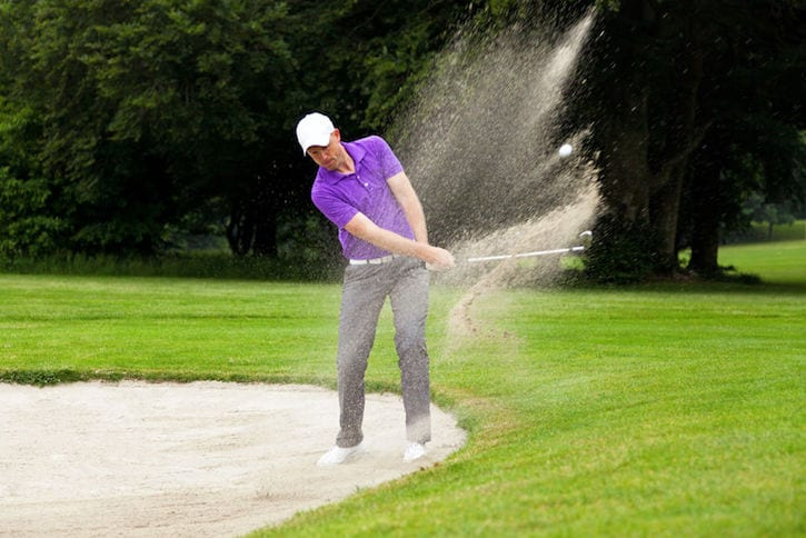 24880989 - a professional golfer hitting his ball out of a bunker with the sand and ball in mid-air.