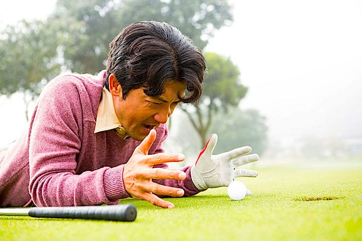 44816942 - golfer lying near golf ball at golf course