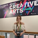 "Student standing in front of ""Creative Arts"" Sign"