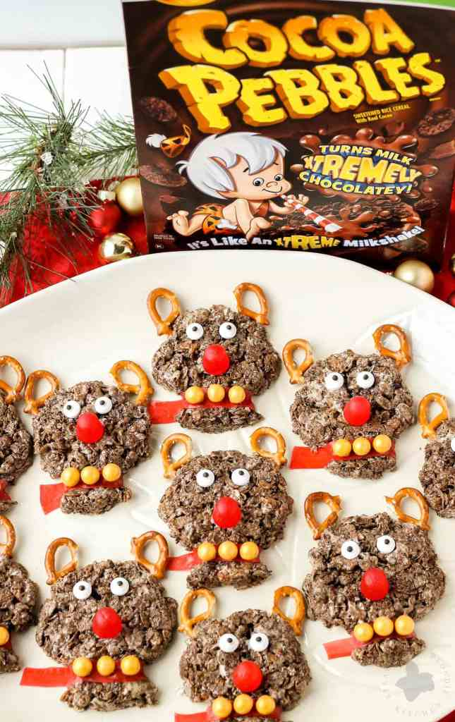 Delicious and {almost} too adorable to eat, these Rudolph the Red Nosed Reindeer Cocoa Pebbles Treats will joy and delight kids and adults alike. We can't forget about Rudolph the Red Nosed Reindeer, after all he is the one who guides Santa's sleigh. These Cocoa Pebbles treats are fun for all your holiday parties this season and they taste great too! | Strawberry Blondie Kitchen