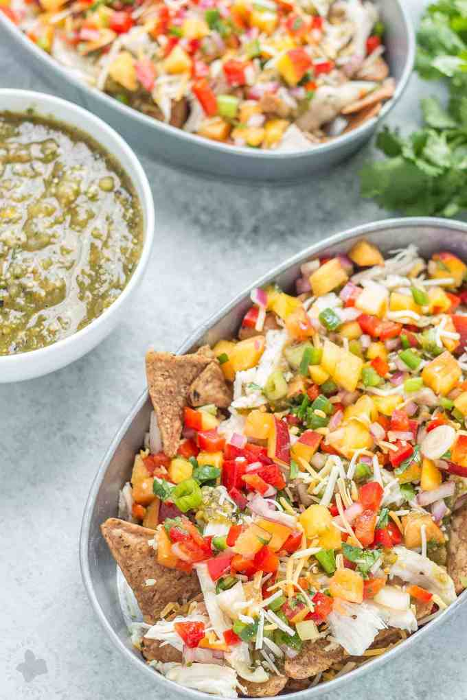 Chicken Nachos with Peach Salsa are bursting with bright summer flavors. Featuring juicy, ripe peaches, fresh chopped veggies and herbs, perfectly cooked chicken and a homemade tomatillo sauce, these nachos will have skipping the taco stand! | Strawberry Blondie Kitchen