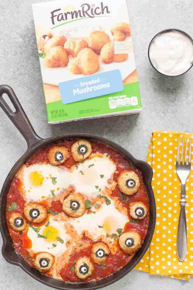 Eggs are baked in a tomato sauce and then breaded mushrooms with sliced black olives, made to looks like eyes, are nestled alongside to create this Halloween Eyeball Skillet. A festive meal sure to please the entire family!
