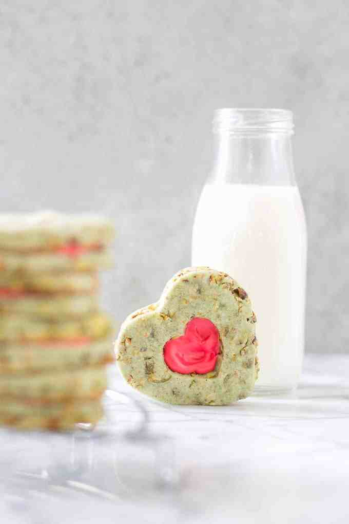 Your heart will grow three sizes with one bite of these Grinch Sandwich Cookies.  Pistachio shortbread cookies, with heart cutouts and red icing pay homage to one of childhood's favorite movies. | Strawberry Blondie Kitchen