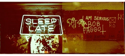 street art graffiti by bob faggot and a bars neon sign which reads sleep late in NYC