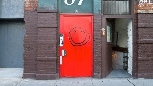 a smiley face drawn on a door on houston street in NYC