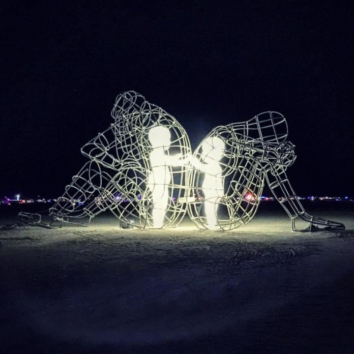 On Burning Man by Alexander Milov – Two adults back to back