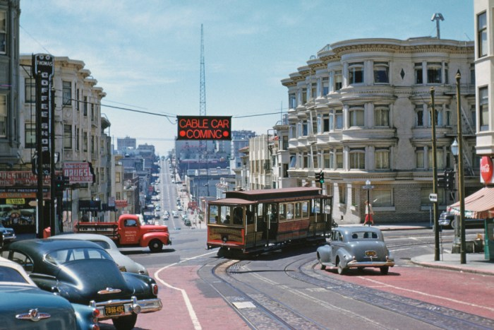 Downtown-bound O'Farrell, Jones & Hyde cable car No. 57 swings 'wrong-way' from Hyde into the oncoming traffic of Pine Street, (1954). The overhead neon sign warns motorists that an eastbound cable car is invading the one-way westbound street for two blocks, before it turns south on Jones Street. This mechanism was set up when the City made Pine one-way. Downtown interests longed to do the same with O'Farrell Street where two automobile garages were being built. The pressure for a one-way downtown street grid helped doom this fabled cable car line, which shut down two weeks after Walt Vielbaum took this great photo.