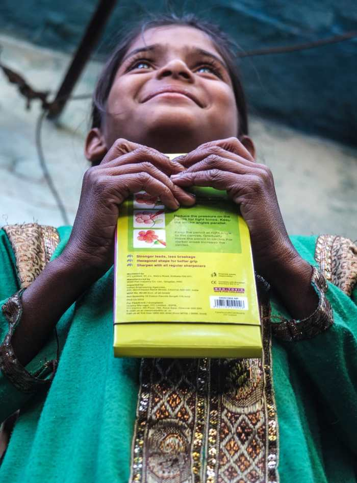 The little girl's eyes sparkle as she receives a gift, in India