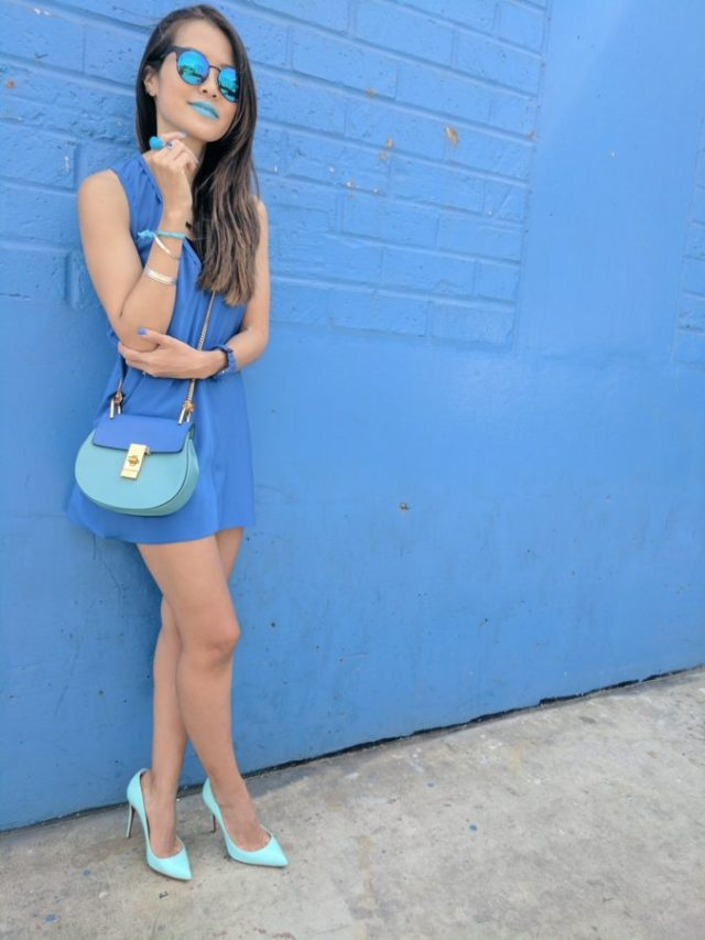 girl wearing blue standing in front of blue wall