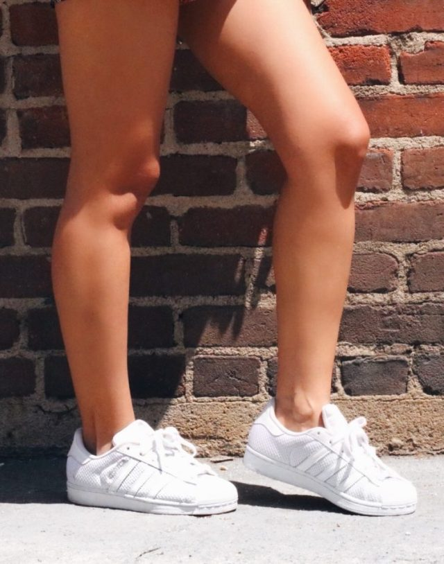 legs and white adidas superstar