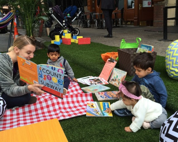 Kristy Raffensberger of the New York Public Library reads to children in a Park(ing) Day space in Tribeca. Photo: HR&A Advisors