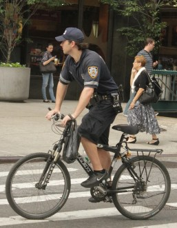 An NYPD officer rides without a bike helmet. Photo: Liz Patek/Flickr
