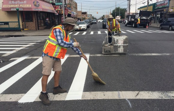 Crews stripe crosswalks on Pitkin Avenue. The bike lane is up next. Photo: Stephen Miller