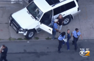This driver, being aided by EMTs, does not face any charges or traffic tickets after running a red and killing a woman on the sidewalk. Image: WCBS