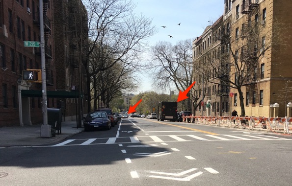 Seaman Avenue at W. 215th Street, looking south at the northbound bike lane, southbound sharrows, and double-parked vehicles …