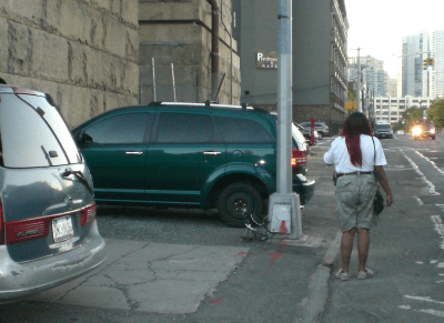 Around the corner, on Vernon Boulevard, illegally-parked cars continue to force pedestrians into oncoming traffic. Photo: Ray Normandeau