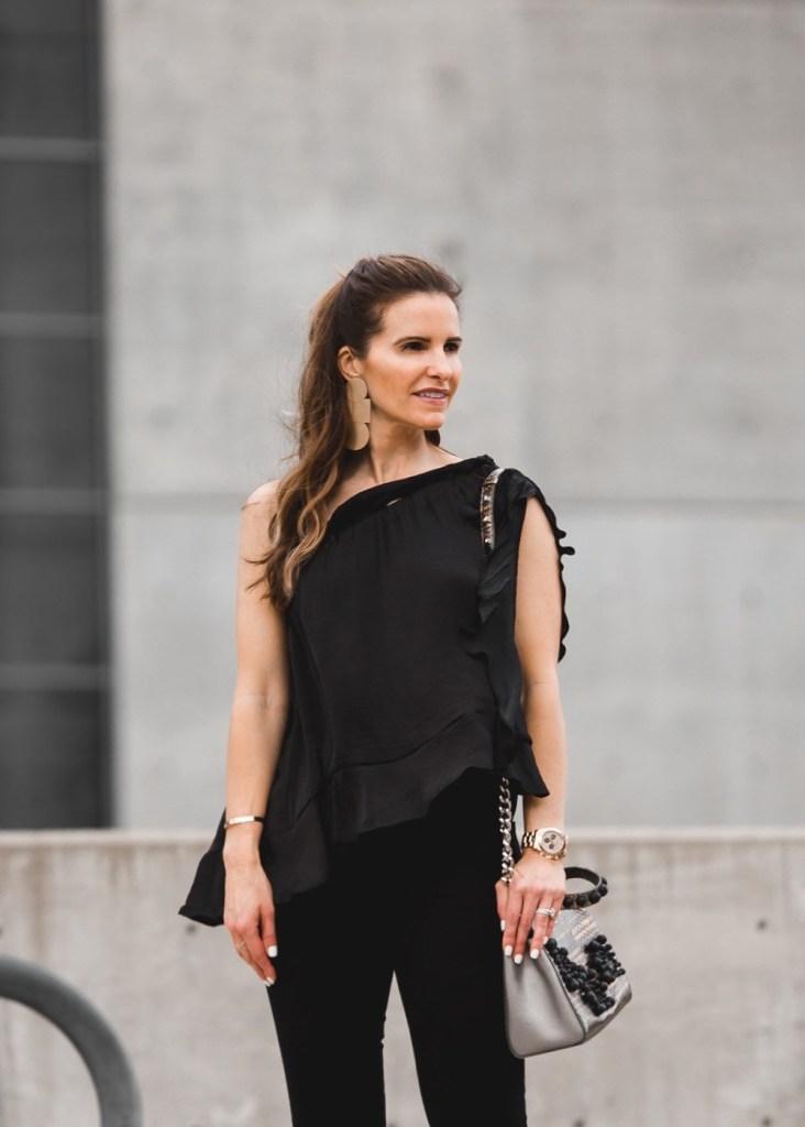 black silk one shoulder top// black jeans// gold drop earrings// silver handbag