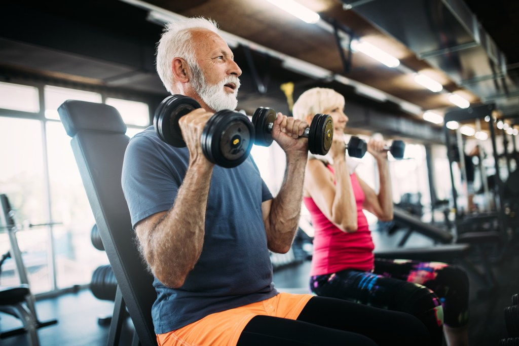 Elderly senior man and woman training with free weights.